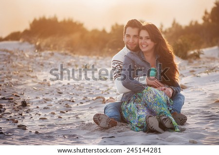 Lovely young couple on the sunset beach, selective focus - stock photo