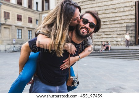 Lovely young couple piggyback in Florence. Italy