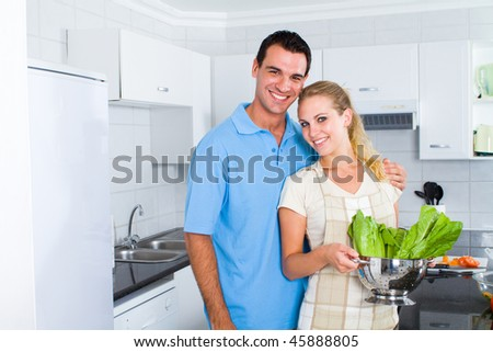 lovely young couple portrait in modern kitchen - stock photo