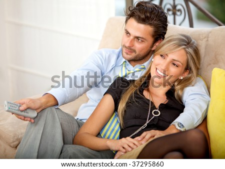 Lovely young couple relaxing watching tv and smiling - stock photo