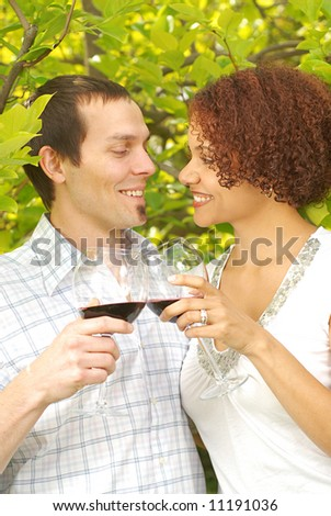 Lovely young couple sharing a drink together at a sunlit park - stock photo
