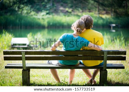 lovely young couple sitting on seat bench with view to lake - stock photo