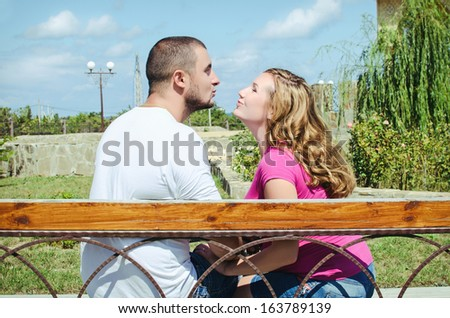 lovely young couple sitting on seat bench with view to summer park. Happy romantic couple on a date outdoors. - stock photo