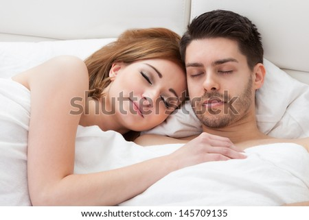 Lovely young couple sleeping on the bed - stock photo