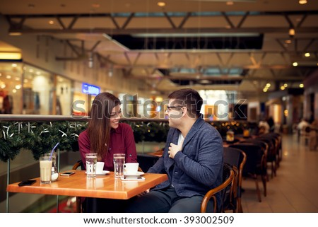 Lovely young couple talking and looking each other at cafe in trade center. Copy space for your text. Shallow depth of field. Very useful photo for processing with one click on edit image. - stock photo