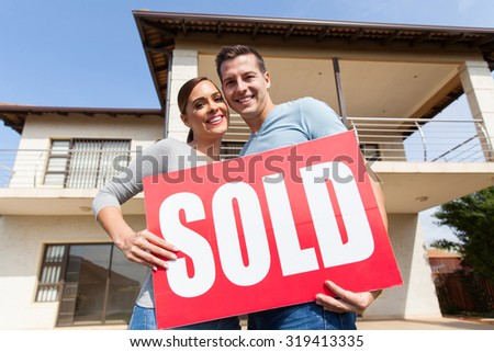 lovely young couple with sold sign in front of their old house - stock photo