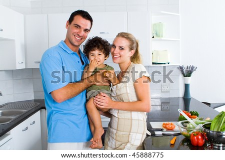 lovely young family in modern kitchen - stock photo