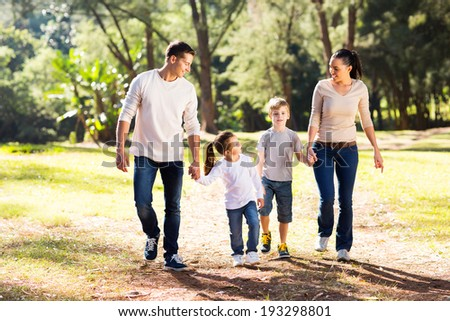 lovely young family walking hand in hand in forest - stock photo