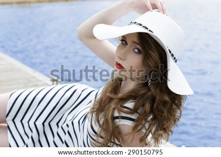 lovely young female with trendy summer striped dress and hat lying on wood jetty near blue sea water. Looking in camera with charming expression and stylish make-up.  - stock photo