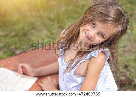Lovely young girl reading a book outdoors