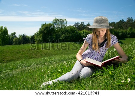 Lovely Young Girl Reading A Book While Sitting In A Beautiful Field Of Grass - stock photo