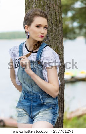 lovely young girl with casual cloche posing in the nature near tree with lake water on background. Fashion girl in vacation - stock photo