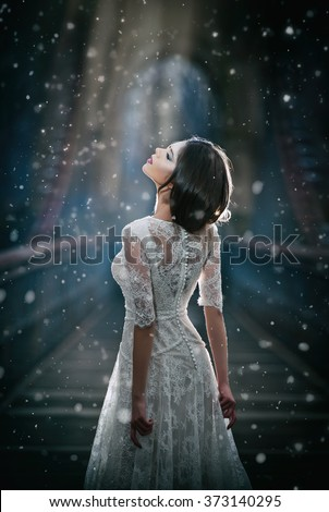 Lovely young lady wearing elegant white dress enjoying the beams of celestial light and snowflakes falling on her face. Pretty brunette girl in long wedding dress posing on a bridge in winter scenery