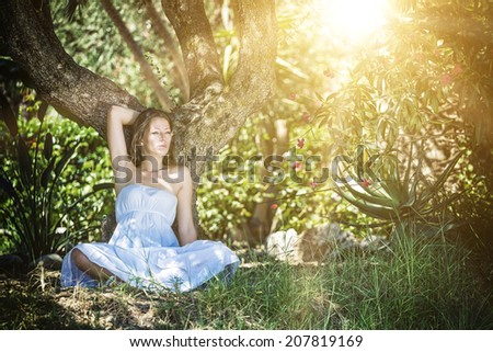 Lovely young lady wearing elegant white dress relaxing in the forest  - stock photo