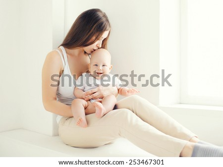 Lovely young mom kissing her baby at home in light room - stock photo