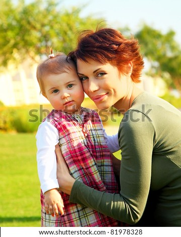 Lovely young mother and cute little baby girl closeup portrait, happy family outdoor
