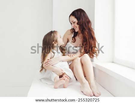 Lovely young mother and daughter having fun at home in white room near window - stock photo