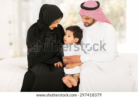 lovely young muslim family of three sitting at home - stock photo
