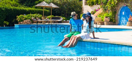Lovely young romantic couple relaxing by swimming pool - stock photo