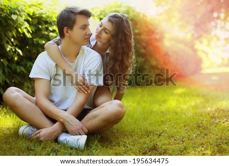 Lovely young teen couple in love having fun on lawn in park, in summer sunny day - stock photo