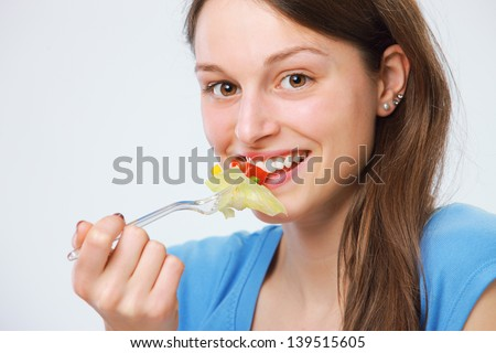 Lovely young woman enjoying a mouthful of salad - stock photo