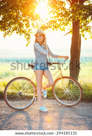 Lovely young woman in a hat riding a bicycle in a park. Active people. Outdoors - stock photo