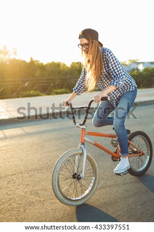 Lovely young woman in a hat riding a bicycle on city background in the sunlight outdoor. Active people