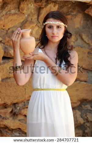 Lovely young woman in a long white dress in Greek style keeps ancient amphora to the ancient site Nymphaeum, village Geroevskoe, Republic of Crimea, Russia - stock photo