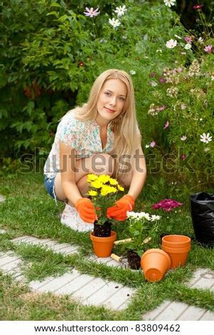 Lovely young woman planting flowers in the garden - stock photo