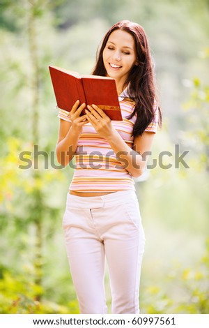 Lovely young woman reads book in green summer garden. - stock photo