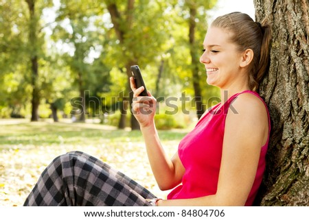 lovely young woman reads sms on mobile phone
