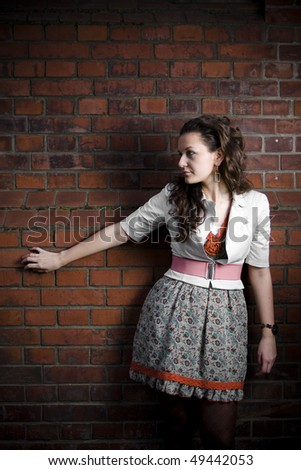 Lovely young woman sitting next to a rusty brick wall. One single light used.