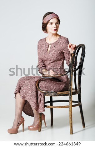 Lovely young woman sitting on a chair. Portrait in retro style - stock photo
