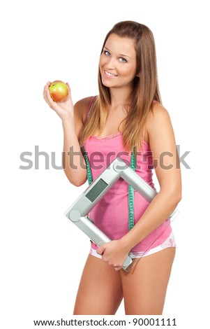 Lovely young woman standing and holding apple and weight scale, isolated on white