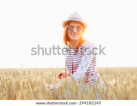 Lovely young woman stands in a field with her bicycle. Lifestyle concept - stock photo