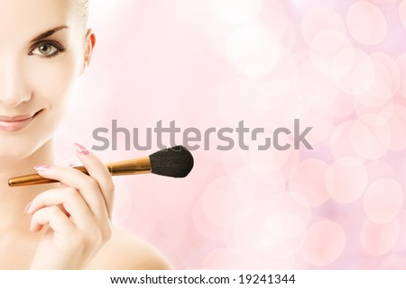 Lovely young woman with a make-up brush