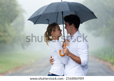 lovely young woman with boyfriend under an umbrella in the rain - stock photo