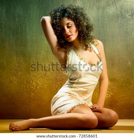 Lovely young woman with curly hair indoors - stock photo
