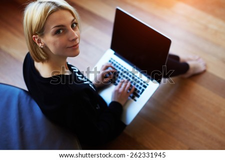 Lovely young woman working on laptop computer at home, attractive blonde hair student using laptop in her living room and look to the camera, female freelancer working at home - stock photo