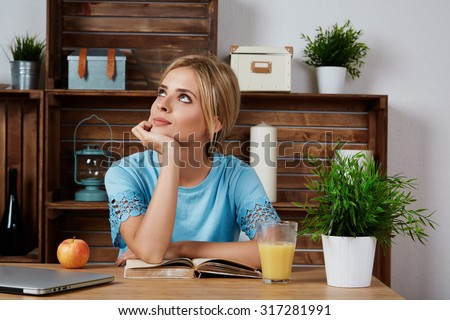 Lovely young woman working on laptop computer at home, attractive blonde hair student using laptop in her living room, female freelancer working at home - stock photo
