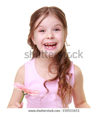 Lovelyl little girl with a sweet smile holding a beautifu flower on a white background