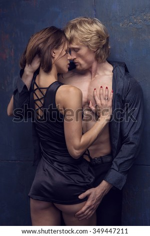 Lover couple. Passionate kissing, hugs. Man and woman standing on a stone wall background. Love relationship in a pair of man and woman. Images of the novel about love. Woman dreams. Man's instinct.