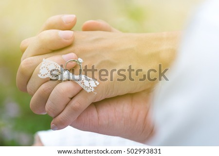 Lover hands hold together in the beautiful garden. Romantic lover theme outdoor with warm tone color filter.