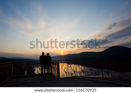 lovers admire the sunset in the mountains - stock photo