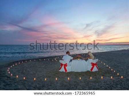 Lovers couple have a romantic dinner with heart of candles on tropical sandy sea beach - stock photo