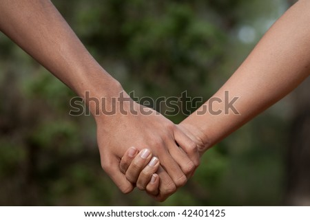 Lovers couple holding hands in a forest (summer/spring) - stock photo