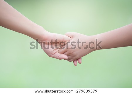 Lovers couple holding hands in green background