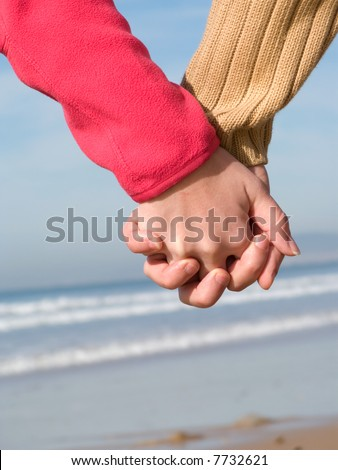 Lovers couple holding hands on beach - stock photo