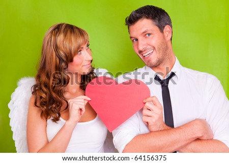 Lovers couple holding red christmas heart - stock photo