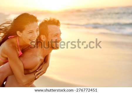 Lovers couple in love having fun piggybacking on date on beach. Portrait beautiful healthy young adults girlfriend and boyfriend hugging happy. Multiracial dating or healthy relationship. From Hawaii. - stock photo
